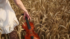 Violinist girl walking through a wheat field. Slow motion Stock Footage