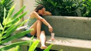 Woman sitting on bench in the garden and crying Stock Footage