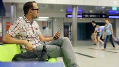 Young man listen to the music on smartphone at train terminal HD Stock Footage