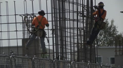 Construction workers rebar and safety harness two shot Stock Footage