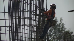Construction worker rebar and safety harness side shot Stock Footage