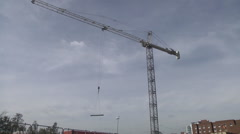 Construction crane on site pan to traffic wide shot Stock Footage