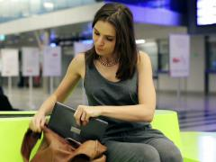 Woman with laptop walk away in hurry for her train at train station NTSC Stock Footage