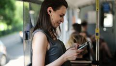Woman listen to music on smartphone during tram ride HD Stock Footage