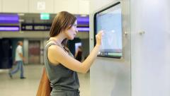 Woman checking trains timetable at modern touchscreen info kiosk HD - stock footage