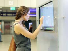 Woman checking trains timetable at modern touchscreen info kiosk NTSC - stock footage
