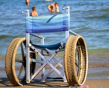 Wheelchair with perforated wheels on the sea beach Stock Photos
