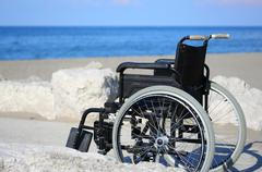 wheelchair on the rocks of the blue sea in summer - stock photo