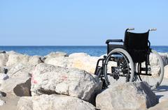 Black wheelchair on blue ocean shore in a sunny summer day Stock Photos
