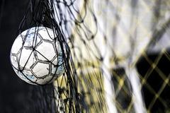 A soccer ball stuck on the net behind goal Stock Photos