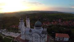 Aerial view over cathedral on countryside in mountains at sunset Stock Footage
