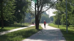woman striding along the path in the park in the morning on the charge - stock footage