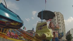 Stock Video Footage of Module from the amusement park turn against the buildings of the city.