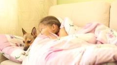 little girl lying on the sofa hugging a dog - stock footage