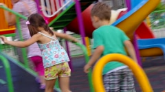 Children playing in the playground with swings and slides. Stock Footage
