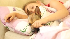 little girl resting on the couch hugging dog - stock footage