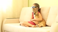 little girl watching TV in 3d glasses hugging a puppy - stock footage