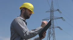 Electrician writing on clipboard outside near high voltage pole engineer working Stock Footage