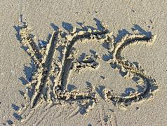 Stock Photo of great written yes engraved on the sand of the sea beach