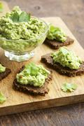 Stock Photo of Pumpernickel slices with a pea and walnut spread on a cutting board