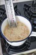 Saucepan with thermometer, sugar, honey and inverted sugar syrup for making Stock Photos
