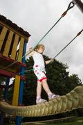 Stock Photo of Little girl balancing on tightrope at climbing crag