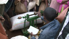 African tradesman Market Scene,  man measures weigh harvest Stock Footage