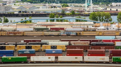 Zoomed in Time Lapse of Train Yard with River Background - stock footage