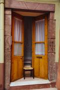 Italy, Sarinia, Bosa, Old door, Ajar with chair - stock photo