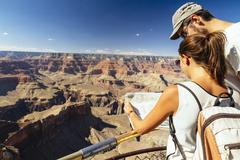 couple with map orientating in front of Grand Canyon - stock photo