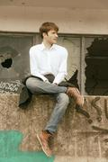 Stock Photo of Hafencity, young man sitting on a wall