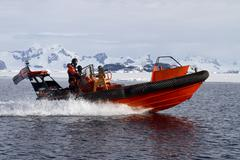 Orange boat sailing at high speed in antarctic waters against mountains Stock Photos