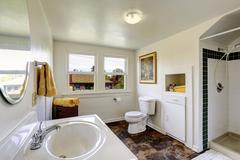 white bathroom with contrast brown tile floor - stock photo