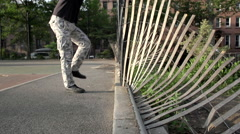 In slow motion, a person climbs a fallen fence Stock Footage
