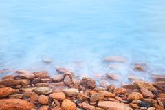 Shore of the sea, stones  and flowing water Stock Photos