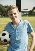 Teenage boy leaning on goal post Stock Photos