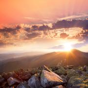Sunset in the mountains landscape. dramatic sky,  colorful stones and sunbeam Stock Photos