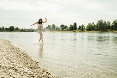 Young woman running at waterside of Rhine river - stock photo