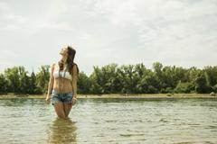 Stock Photo of Young woman relaxing at waterside of Rhine river