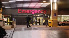 Police unrolling crime tape at hospital entrance Stock Footage
