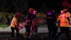 Emergency crew carrying patient in stretcher Stock Footage