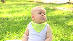 Baby sitting on the grass in the summer park and playing with soap bubbles Stock Footage