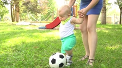 Mom teaches baby to steps first time, play football with the ball at the end of  Stock Footage