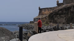 Old man looking at the sea standing on a waterfront sidewalk next to fortress Stock Footage