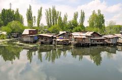 Slum houses near the river, Srinagar, India Stock Photos