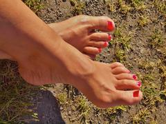 Woman leg with red polished nails lies on old cut grass. Stock Photos