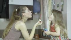 Happy mother and daughter blowing bubbles at home Stock Footage