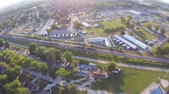 Aerial View of train coming down tracks beside fairgrounds in late afternoon - stock footage