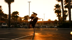 Boy dancing breakdance in front of a shopping mall in the U.S. in the sunset Stock Footage