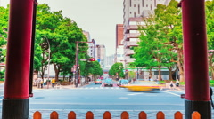 People and cars pass by the gates of Tokyo temple Stock Footage